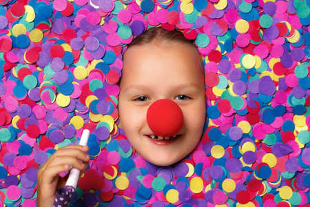 Cheerful cute face of a little girl with a red nose in colorful confetti. The child holds a whistle in his hand.
