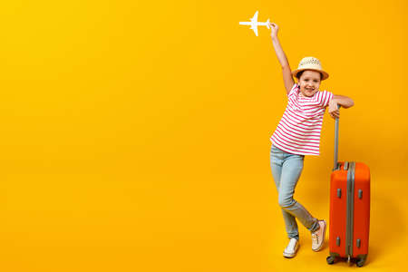 Happy positive little girl holding a paper airplane and dreaming about travel. Child with a suitcase on a yellow background. Copy space.