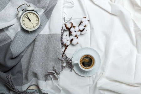 Cozy morning. Breakfast in bed. White and gray bedding, plaid and coffee cup, alarm clock. 免版税图像