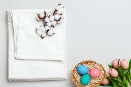 Top view of a stack of white bedsheets sets, cotton branch and a basket with Easter eggs. Copy space. 免版税图像