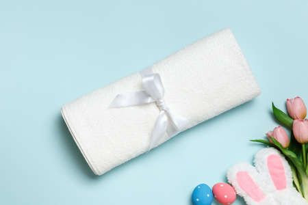 White towel on blue background with bunny ears, Easter and spring celebration concept. 免版税图像