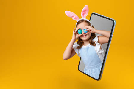 Happy easter. Smiling little girl in rabbit ears holds two eggs and looks out of a smartphone. The child is online in the mobile screen. Copy space. 免版税图像