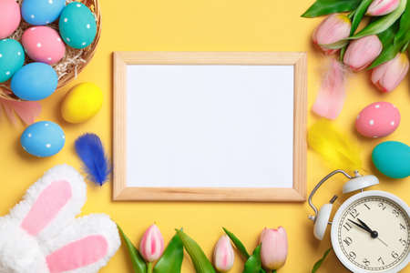 Happy easter. Multicolored eggs, tulips and an alarm clock on a yellow background. Flat lay invitation greeting card with copy space.