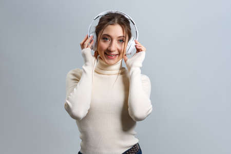 Cheerful girl in headphones standing and listening to music. Beautiful young brown-haired woman on a gray background.