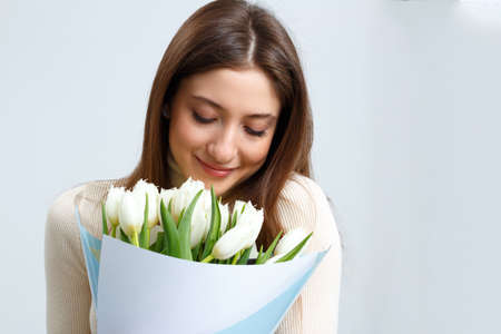 Closeup portrait of young woman holding large bouquet of white tulips on gray background. A beautiful brown-haired girl closed her eyes and breathes in the scent of flowers.
