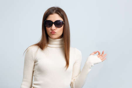 Fashionable girl in sunglasses sends a kiss and shows ok sign on a gray background. Beautiful young brown-haired woman pouted her lips. 免版税图像
