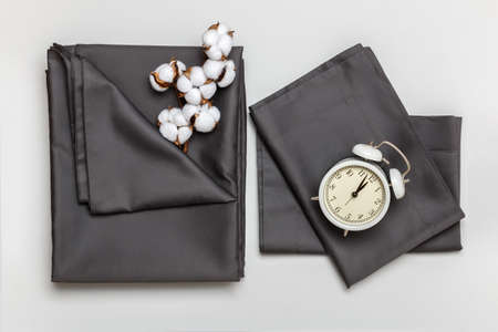 Top view of a set of gray bed sheets, pillow cases, duvet cover, cotton branch and alarm clock. 免版税图像