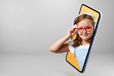 A little girl in glasses and headphones looks out of a smartphone. Child online on a mobile phone screen. Distance learning schoolgirl at home.