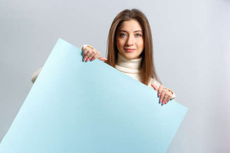 Beautiful girl holding a blank blue banner on a gray background. Young brown haired woman smiling and looking at the camera.