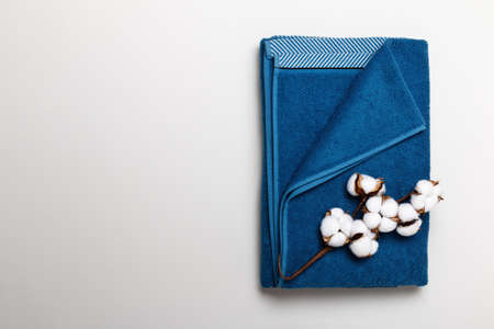 Top view of folded blue towel with cotton branch on gray background.