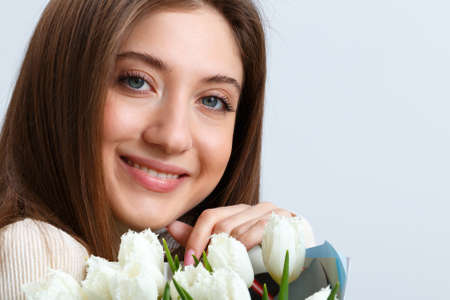 Close up portrait of a beautiful girl holding a bouquet of white tulips. Young woman with charming smile on a gray background. 免版税图像