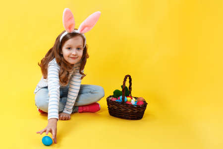 Little girl in bunny ears on a yellow background in the studio. A cute kid sits on the floor with an Easter basket and hunts for an egg.