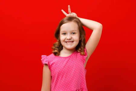 Happy easter. A cheerful child shows the ears of a rabbit with his fingers. Portrait of a little girl on a red background.
