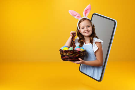A little girl in bunny ears holds a basket with colorful Easter eggs and looks out of a smartphone. Child online on a mobile phone screen. Copy space.