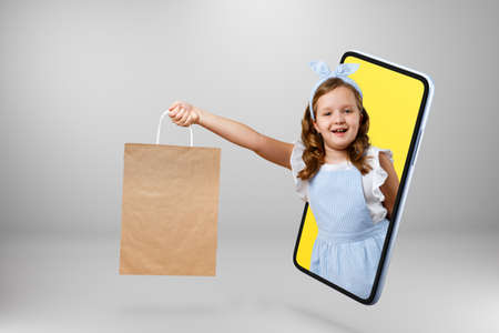 A little girl holds a gift bag in her hand and gets out of the smartphone.