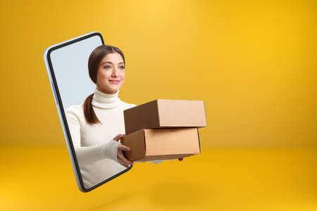 A smiling beautiful girl got out of her smartphone and hands over boxes with orders. Young woman with online shopping on the mobile phone screen. Copy space.
