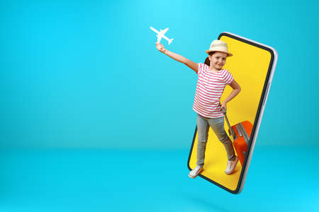 A little girl in full growth with a paper white plane and a suitcase comes out of the smartphone. Child online on a mobile phone screen with copy space.