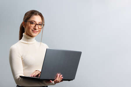 Cute young woman in glasses holds a laptop. Beautiful girl student smiling and looking at the camera on a gray background with copy space. 免版税图像