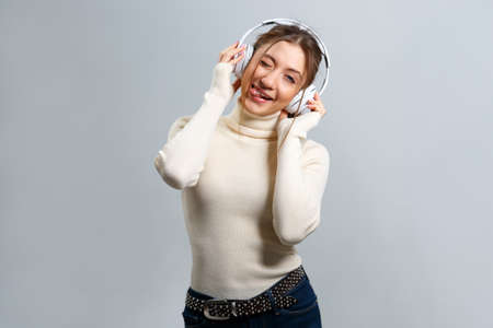 A cheerful girl with headphones listens to music, has fun and shows her tongue. Beautiful young brown-haired woman on a gray background.