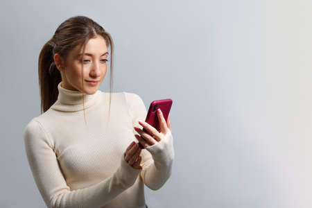 A girl in a sweater looks at the smartphone screen and smiles on a gray background. A young brown-haired woman uses a mobile phone to exchange messages.