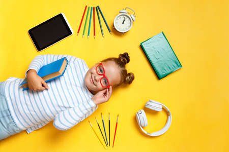 Schoolgirl little girl in glasses with a book lies on a yellow background. Top view of a child student surrounded by a tablet, pencils, alarm clock and headphones. 免版税图像