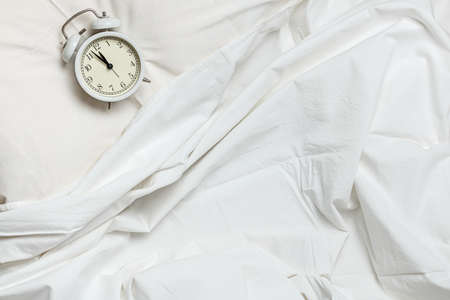 Top view of white bed linens and an alarm clock on a pillow.