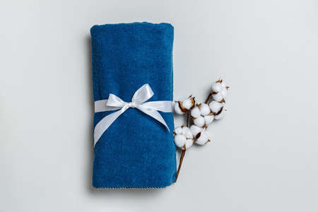 Top view of rolled up blue towel with cotton twig on gray background with copy space.