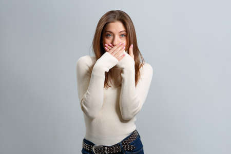 Surprised beautiful girl covers her mouth with her hands and looks at the camera. A young brown-haired woman crossed her palms in front of her lips on a gray background.