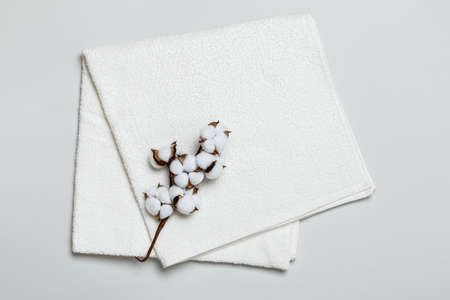 Close-up top view of folded white towel with cotton twig on gray background.