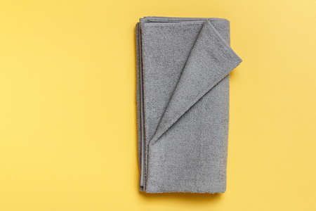 Close-up on a gray folded towel against a yellow background. Flat lay top view copy space. 免版税图像