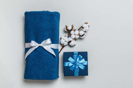 Top view of rolled blue towel with cotton sprig and gift box on gray background with copy space.
