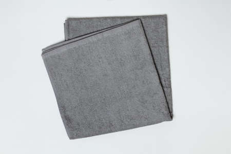 Gray folded towel on a white background. Close-up flat lay top view.