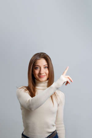 Smiling girl points a finger up on a gray background. Happy young woman in a white sweater with her hair down. 免版税图像