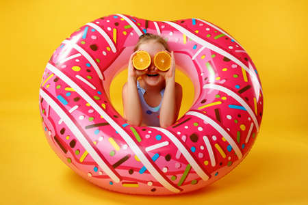 Summer concept. Little girl with halves of an orange lying on an inflatable donut circle. Child in the studio on a yellow background.