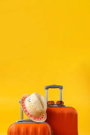 Summer time concept. Close up of two travel bags suitcases, straw hat and sunglasses on yellow background with copy space.