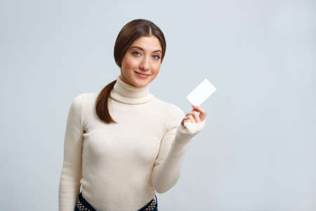 Beautiful girl holding a business card on a light gray background. Young woman smiling.