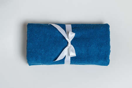 Top view of a rolled up terry blue towel on a light gray background.