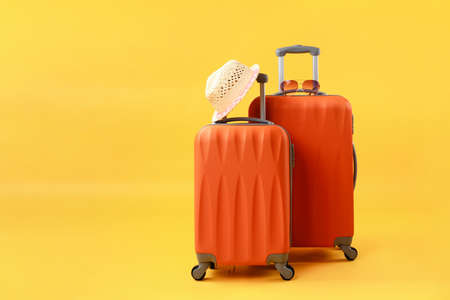 Two suitcases of travel bags, straw hat and sunglasses on yellow background with copy space. Concept of summer time, vacation, tourism.