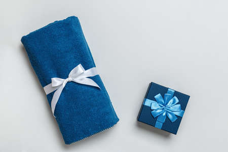 Top view of rolled terry blue towel and gift box on light gray background with copy space.