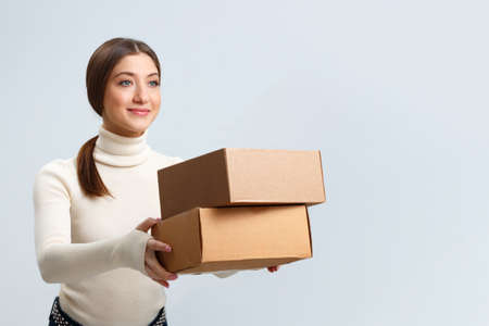Smiling beautiful girl hands over boxes with orders. Young woman with purchases. delivery