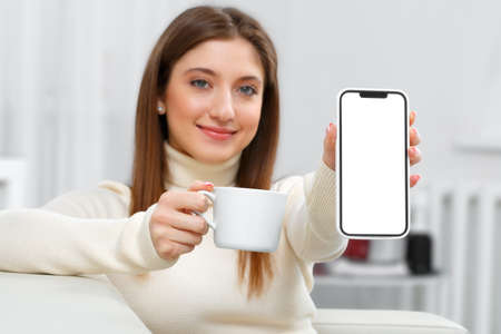 Smiling girl sitting on the couch at home with a cup of coffee. Happy young woman shows a mobile phone with a white touch screen.