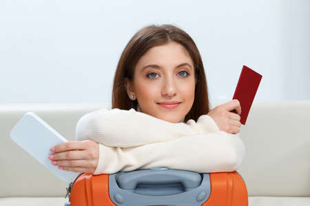 Beautiful happy girl with a suitcase and a passport on a gray background. Travel and vacation concept. 免版税图像