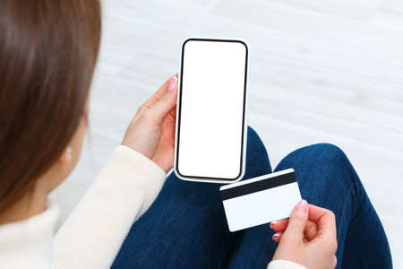 The girl holds a smartphone and a credit card for payment. Young woman is shopping online. 免版税图像