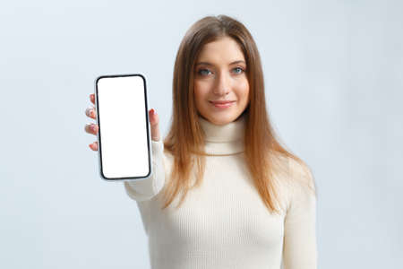 Smiling young woman showing smartphone with white touch screen mockup. Beautiful brown haired girl on a gray background.