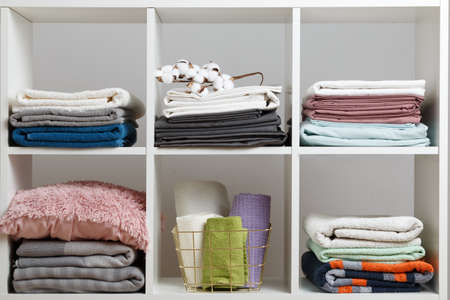 Stacks of towels, sheets, bed linen, blankets and pillows on a white shelf.