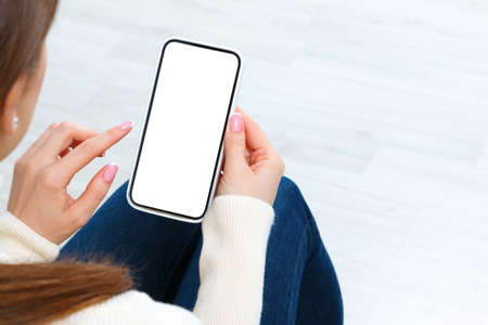 Back view of girl holding smartphone with white blank screen mockup. Lifestyle concept with digital technology.