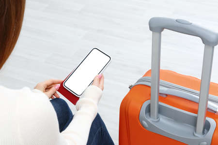 Back view of girl holding smartphone with white blank screen mockup. Traveler with phone at the airport with passport and suitcase. Lifestyle concept with digital technology.