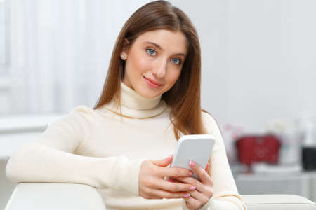 Smiling girl sitting on the couch at home uses a mobile phone. Happy young woman holding a smartphone and looking at the camera.