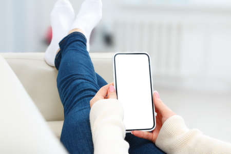 Back view of girl lying on sofa holding smartphone with white blank screen mockup. Lifestyle concept with digital technology.