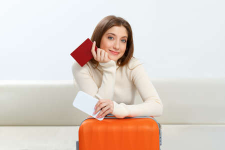 Beautiful happy girl with a suitcase and a passport is sitting on the couch while waiting for the flight. Travel and vacation concept.